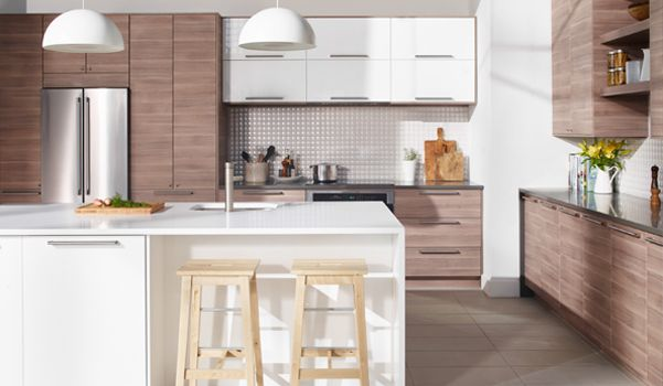 A large modern SEKTION/BROKHULT kitchen in walnut effect light grey with high stool