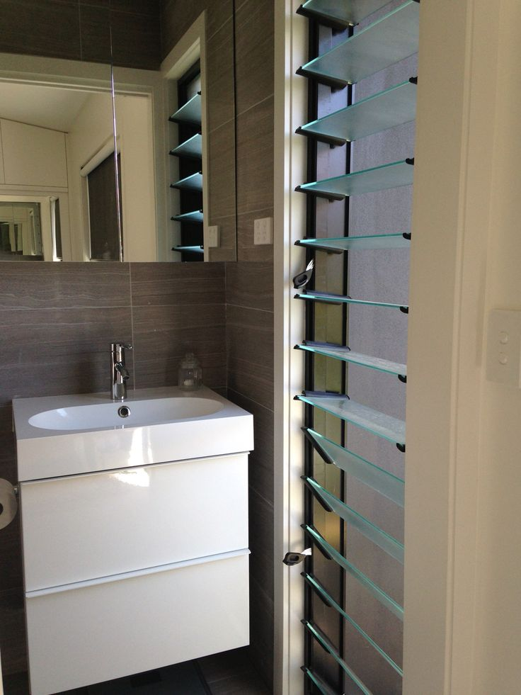 Bathroom in Granny Flat / She shed / Man Shed / Home studio / Home office in Bondi Beach by Hannah Duke Interiors.  A towel rail was added to the inside of the louvres - nicely dries the towels.