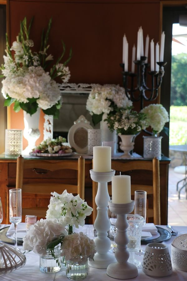 a large collection of white candleholders and other props