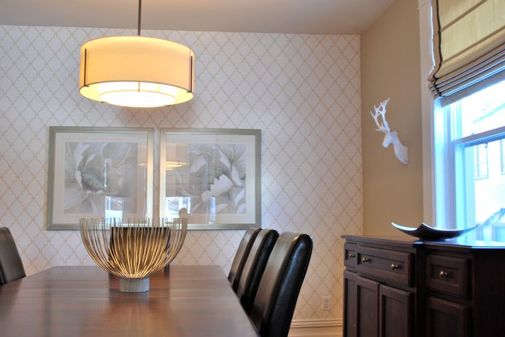 Trellis wallpaper sets the stage illuminated dining room. Large artwork can be seen from the living room and dining room. Large pendent light above seems to light up the sculptural bowl below.
