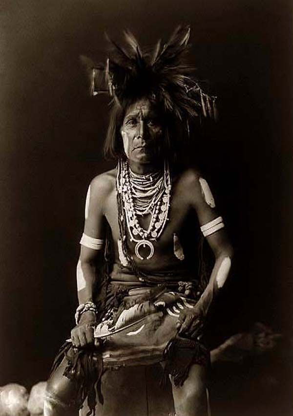 You are looking at an educational picture of a Snake Indian Priest. It was taken in 1900 by Edward S. Curtis.  The picture presents a Native American man seated, three-quarter-length, facing front.