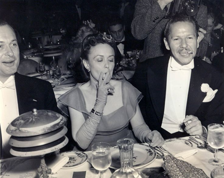 Robert Montgomery and his wife, Elizabeth Bryan Allen, and character actor Roger Pryor attending a clambake at the Cocoanut Grove in the 1940s.   Two other items were noting:  Montgomery and Allen were the parents of Bewitch's Elizabeth Montgomery.   This candid was believed to have been taken by George Hurrell.