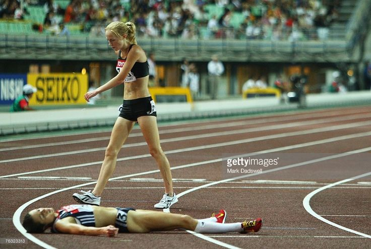 Kimberley Smith of New Zealand walks past Jo Pavey of Great Britain as she lays exhausted after competing in the Women's 10,000m final on day one of the 11th IAAF World Athletics Championships on August 25, 2007 at the Nagai Stadium in Osaka, Japan.