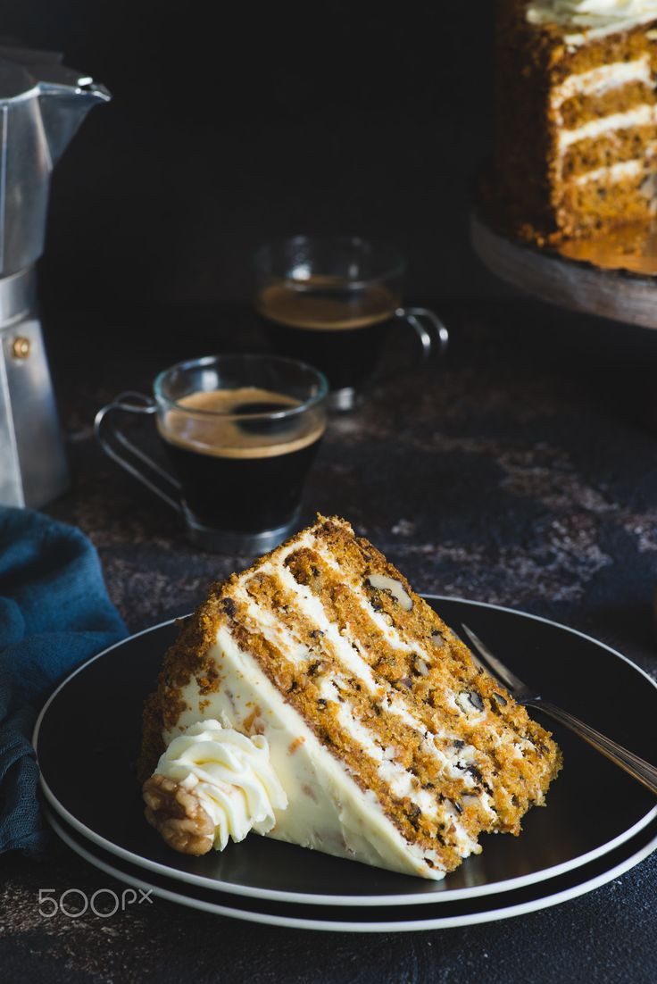 Slice of carrot cake - Slice of carrot cake with walnuts on black plate served with coffee, over dark background, vintage look, closeup