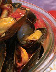 Dans une casserole vaporisée d'huile d'olive, faire revenir l'oignon vert, l'oignon et l'ail environ 1 minute. Ajouter les moules et le vin blanc. Couvrir. Cuire de 3 à 4 minutes.  Incorporer la sauce tomate et poursuivre la cuisson à couvert de 3 à 4 minutes. Quand les moules sont ouvertes, elles sont cuites.