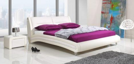 Łóżko tapicerowane Calgary w kremowej tapicerce obok stoliczek nocny .