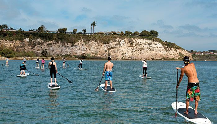 Sup Stand Up Paddle Boarding Is A Fun Activity And A Good Exercise Out On The Water Vacation Activities Beach Activities Beach Local