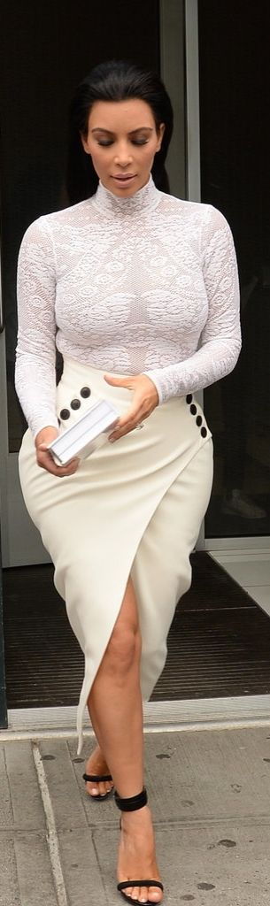 Kim Kardashian signed copies of her book, Selfish, wearing a white mesh embroidered turtleneck, asymmetrical midi skirt, and black ankle strap sandals.