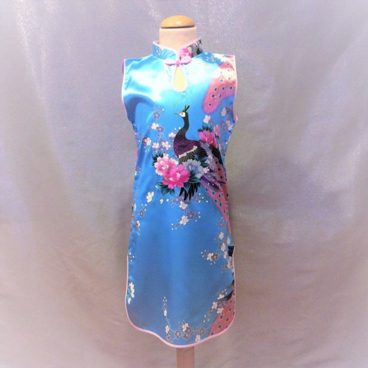 Turquoise Chinese jurk met 1 knoopsluiting op de hals. Smal model met rittsluiting onder de oksel in het zijpand. 100% polyester zonder stretch.  Model: Mulan