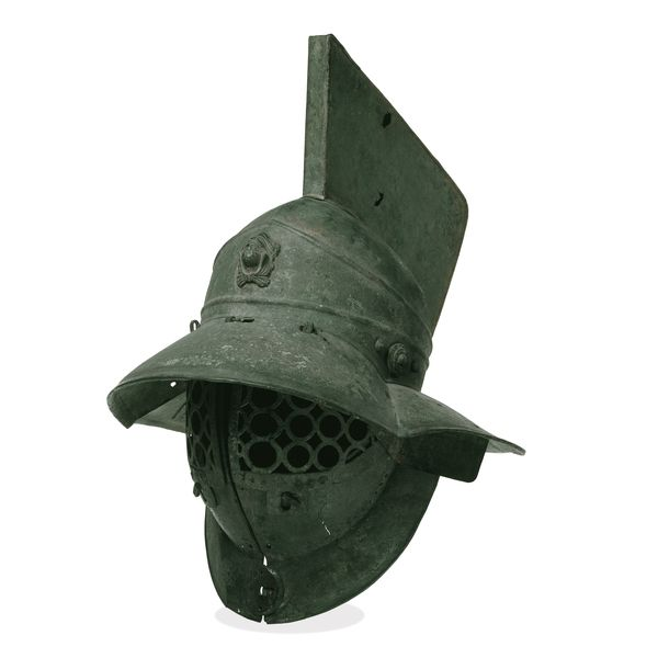 A 1st century CE Bronze Gladiator helmet of the Samnite class. Roman gladiator helmets were richly decorated and plumed with ostrich or peacock feathers. This relatively plain example has the embossed head of Hercules at the front. Provenance: Pompeii. (British Museum, London)