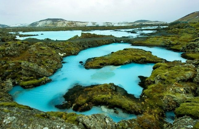 """Blue Lagoon Iceland - Iceland is a place of stunning wonders, like glaciers, volcanoes, geysers, fjords and beautiful lagoons filled with healing geothermal seawater — not to mention the 13 different kinds of elves that inhabit The Blue Lagoon falls under the """"healing geothermal seawater"""" category; its namesake, blue-hued waters are not only gorgeous to look at, but they are praised by many for their deeply salubrious nature."""