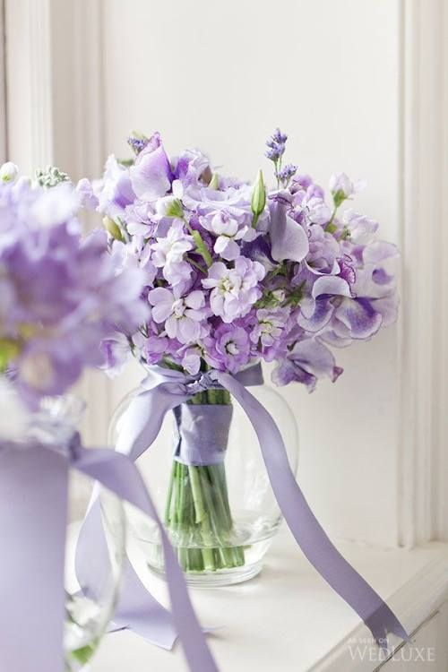 Beautiful lavender flowers tied with ribbon above the water line with the ribbon trailing outside the vase on Southern Dawn.