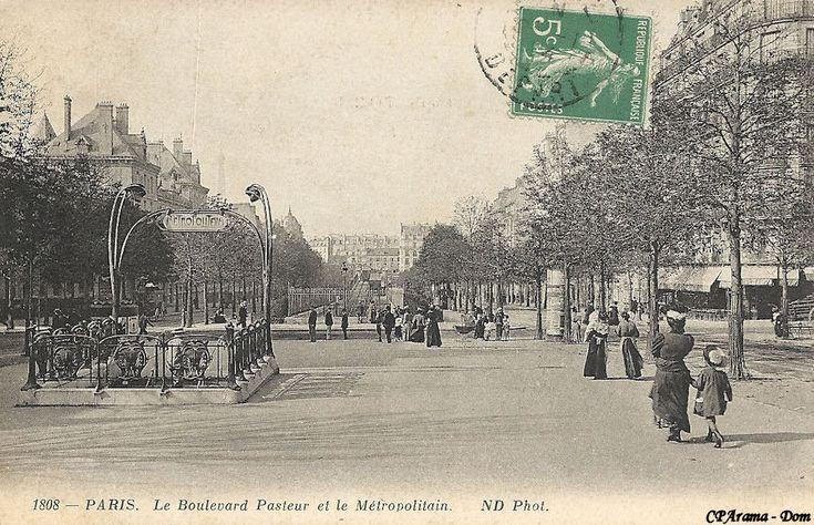 """Le boulevard Pasteur, à gauche le lycée Buffon, au fond la sortie de terre du métro qui devient aérien (Ligne 2 Sud), et au premier plan, l'entourage Guimard de la station avec ses candélabres caractéristiques et la plaque émaillée """"Métropolitain"""". La station est ouverte en avril 1906, lors du prolongement de la ligne de Passy à Place d'Italie."""