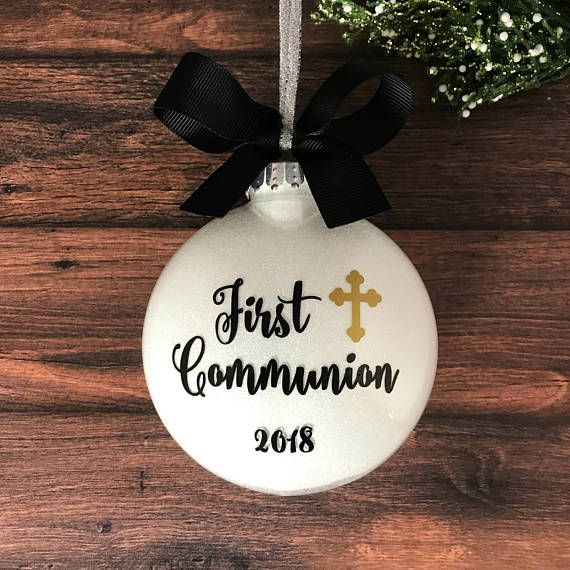 This beautiful 1st Communion ornament features a gold metallic cross, black vinyl script lettering, a sparkly white glitter background, and is topped with a black grosgrain bow. The back of the ornament can be personalized with a first name and/or date making it a cherished gift or