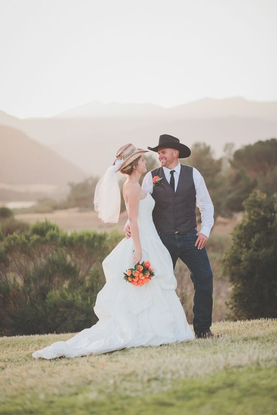 Bride and Groom Portraits at sunset. Bride is wearing a cowboy hat with a veil. Groom has a cowboy hat and boots. June Wedding at Lake Casitas, Ojai, CA. Photo By: Nicole Wasko (www.nicolewasko.com)