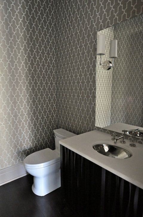Amazing powder room design with white & charcoal gray moorish tiles wallpaper, espresso stained bathroom cabinet, hammered metal sink and polished nickel sconces & faucet.