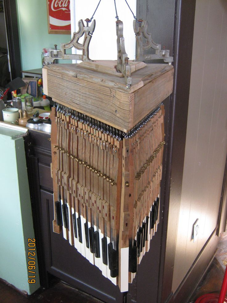"""Reclaimed Piano Hanging Light.  Parts/Specs  -Made with repurposed Piano Parts from a single piano.  -Triangular Body built from a reclaimed Telephone Pole.   -72 Handmade tiny steel """"S"""" hooks  - 6 Dowels to reinforce the body, made from Piano Mallets  - 3 Repurposed Steel Hangers/ Piano Brackets  - 72 Piano Keys"""