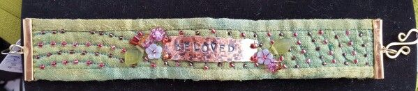 """Cuff, hammered copper with the word """" beloved """" with glass beads on quilted hand dyed silk. OOAK, $50.00. By Heather Thomas"""