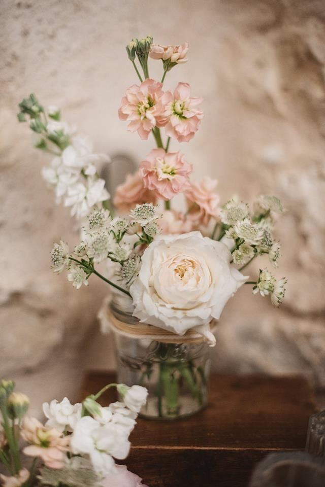Jam jars filled with blush stock and frilly garden roses