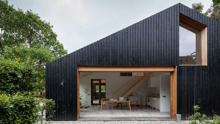 Modern House- Barn | Workshop Architecten has created a blackened wood barn for a farm in the Netherlands, which is divided into separate living quarters for sheep and people.
