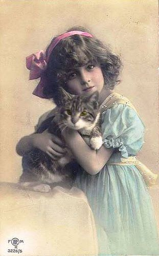 Girl in blue dress and pink hair ribbon, with her cat.