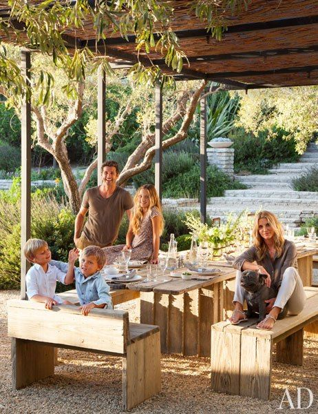 Patrick Dempsey and his wife, Jillian, are joined by their children—daughter Talula and sons Darby and Sullivan—and their French bulldog, Horton on the dining terrace of their Malibu home.