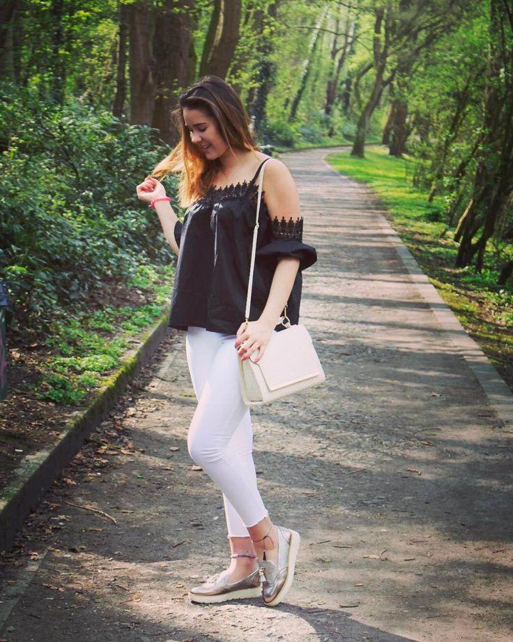 @fannashion mit einer weißen Skinny Jeans, schicken Flatforms in Silber, einer cremefarbenen Handtasche und einer schwarzen Off-Shoulder Bluse mit Spitze aus dem Online-Shop von Ital-Design.