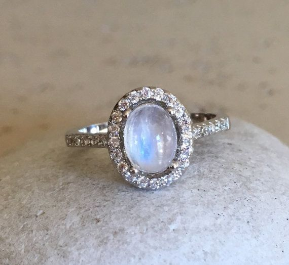 A lovely Halo Setting featuring an oval shaped cabochon Rainbow Moonstone embellished with pave set cubic zirconia in Sterling Silver. Wrapped in a