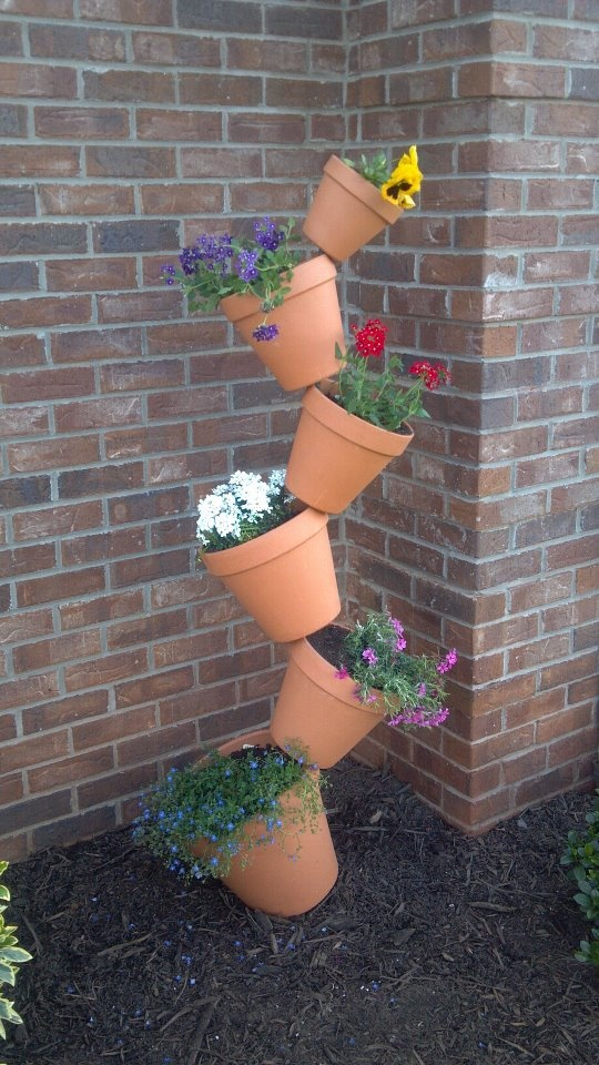 did this in one of my flower beds Looks So COOL!!!!  It's a rebar stake driven into the ground, then you just stack the pots on top of each other(the pots have holes in the bottoms).