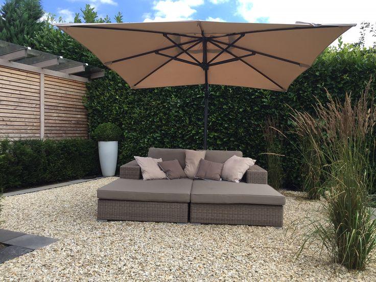 Tuin met grind en groot ligbed met luxe parasol