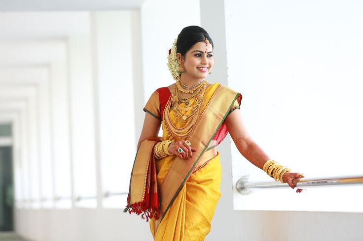 South Indian bride. Gold temple jewelry. Jhumkis.Yellow silk kanchipuram sari with contrast red blouse.Braid with fresh jasmine flowers. Tamil bride. Telugu bride. Kannada bride. Hindu bride. Malayalee bride.Kerala bride.South Indian wedding.