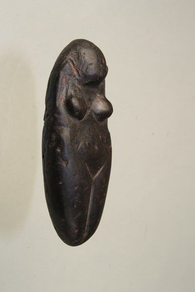 Upper Paleolithic Female Figurine, Eastern Europe, ca. 12,000 B.C.E. carved from black steatite. The abdomen is swollen indicating pregnancy with wide hips and buttocks. Subtle features such as belly button are present along with engraved hair. Remains of red ocher.