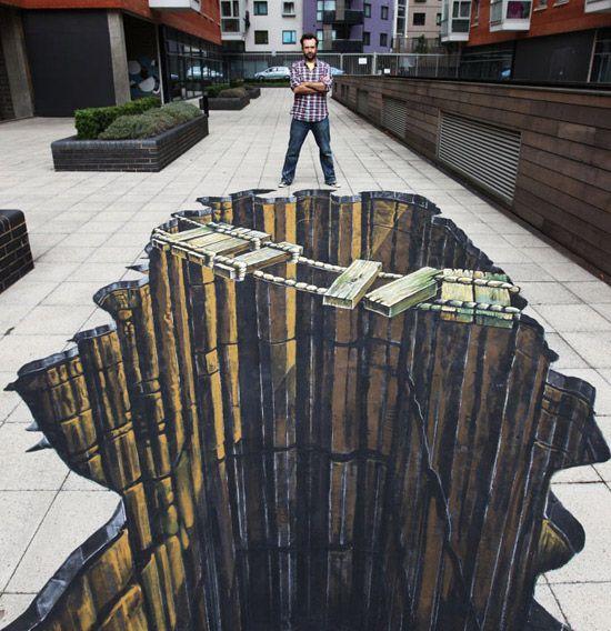 L'oeuvre représente un trou très profond dans le sol et un pont fait avec des planches de bois et de la corde qui n'a pas l'air très solide. L'œuvre est de couleur brune, beige et grise. L'œuvre a été fait dans la rue et l'artiste a utilisé la technique de la peinture, peut-être de l'acrylique. Lorsque je regarde cette œuvre, je me sens apeurée, car j'aurais peur de tomber dans le trou. Finalement, j'aime cette œuvre, car elle est vraiment réaliste!