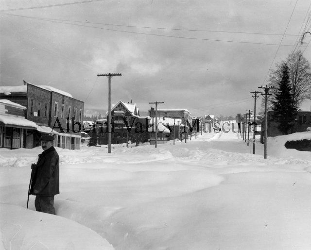 A man stands knee deep in the snow at the foot of Argyle Street in Port Alberni,1913.  Photographer: Leonard Frank.  [Alberni Valley Museum Photograph PN00618]