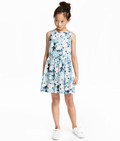 Blue/light pink. Sleeveless dress in cotton poplin. Concealed zip at back, gathered seam at waist, and gently flared skirt. Lined at top.