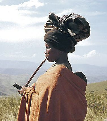 Africa | Xhosa woman with infant and smoking traditional pipe. South Africa | Date and photographer unknown.