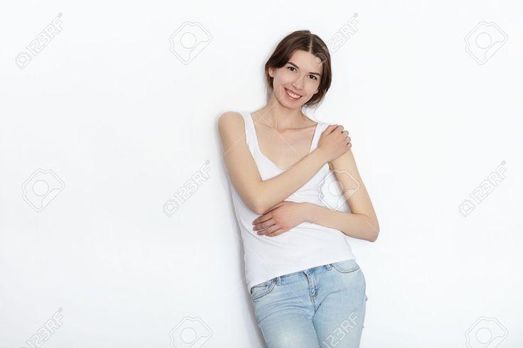 Молодая красивая брюнетка начинающая модель женщина в белой футболке синие джинсы, практикующие позирование, показывая эмоции на белом фоне стены студии Фотография, картинки, изображения и сток-фотография без роялти. Image 80385150.