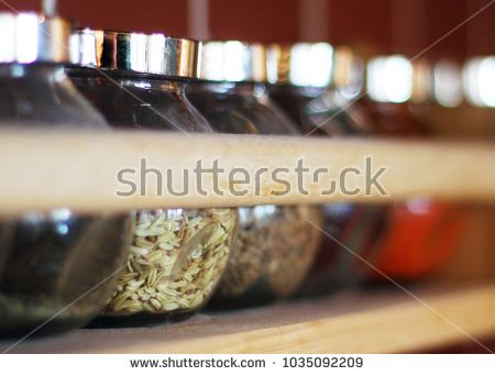 Spices in glass jars on a wooden shelf.