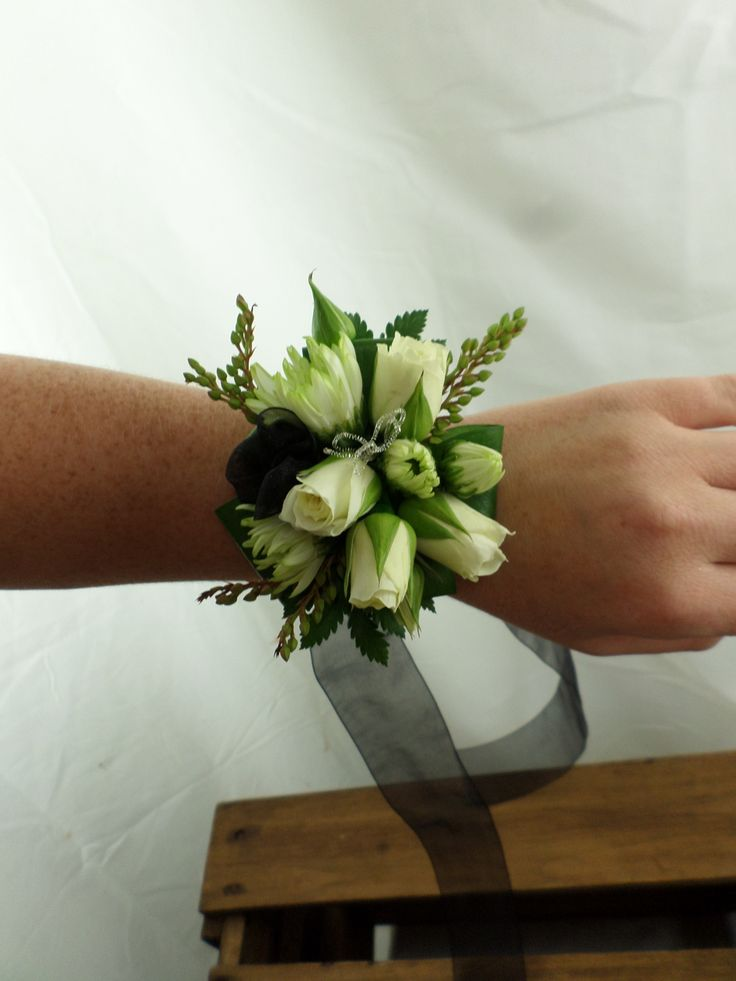 Ball corsage with black ribbon and white and green flowers. Created by Florist ilene