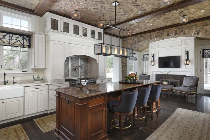 Morgante Wilson Architects designed this kitchen with an exposed brick and beamed ceiling.  The bronze light fixtures from Urban Electric and window treatments made from Kravet fabric add additional character to this detailed space.