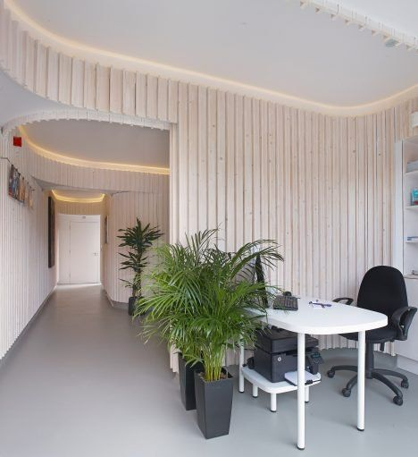 Curving walls made up of vertical strips of bleached wood form the inside of this dental practice in Dublin.