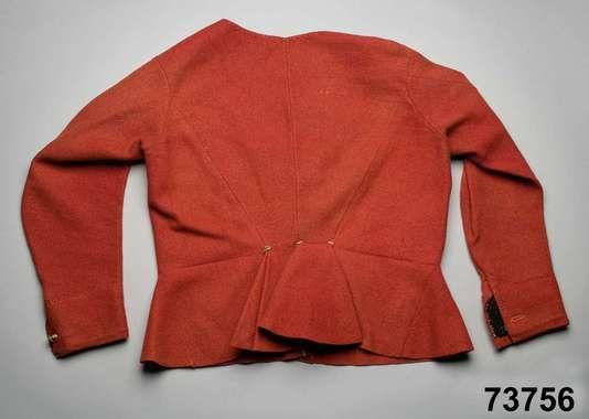 Kvinnotröja av röd vadmal, i 1700-talsmodell med skört och vid halsringning, ofodrad. 2 framstycken/sidstycken med infälld skörtkil i sidan....