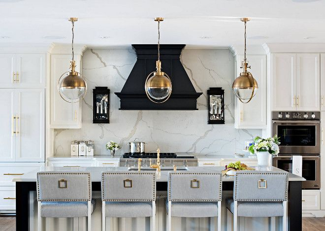 The kitchen cabinets are painted in Benjamin Moore Swiss Coffee and the black hood paint color is Benjamin Moore Onyx. Sarah St. Amand Interior Design, Inc.; Photography by Mike Chajeki.