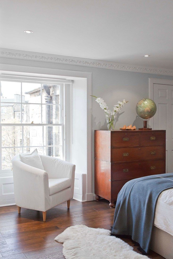 The master bedroom features new floors made of engineered white-oak planks. The campaign-style chest of drawers was purchased at a local antiques shop, and the serene wall color is Farrow & Ball's Skylight.