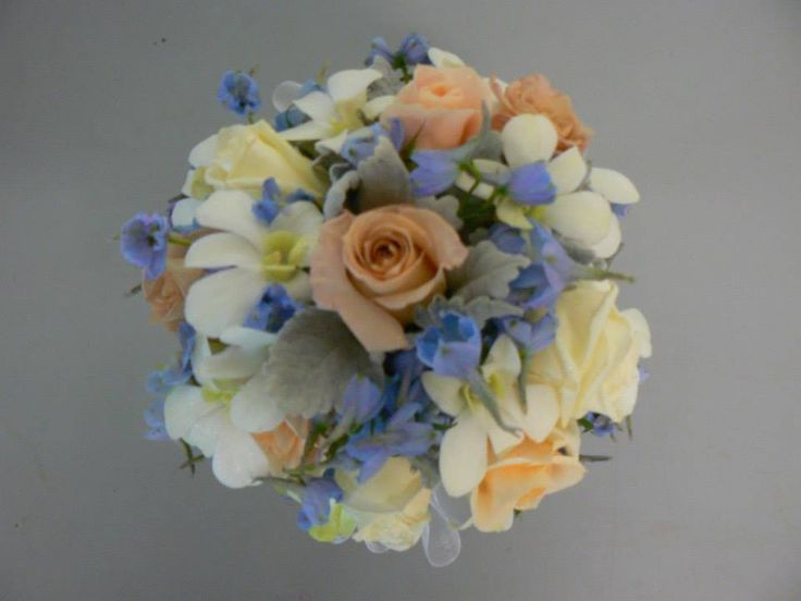 Antique, apricot & cream roses mixed with some pale blue delphinium & white Dendrobium orchids with a dusty miller foliage