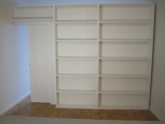 free-standing bookcase divider with hide away pocket door