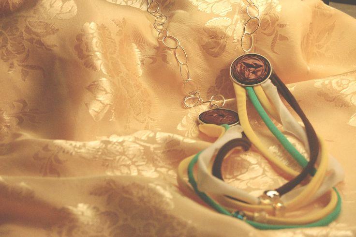 Simona – Prototipo di collana ad ispirazione nordafricana a maglie sottili con lycra pastello multicolore e cialde amaranto. Inserzioni di strass anulari.