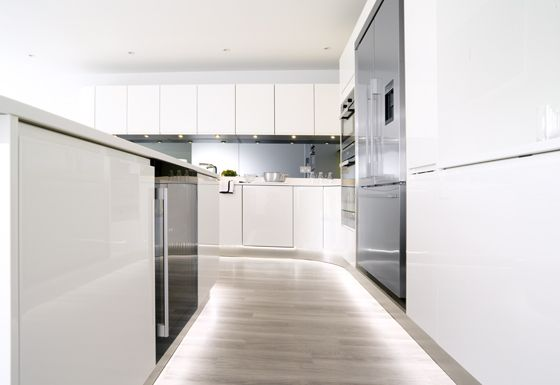 Urban Style curved handle-less kitchen in high gloss white lacquer. Glacier White Corian worktop and Smoke Grey mirrored back-splash. Miele ovens, microwave, induction hob and 2 zone gas hob. Falmec worktop mounted stainless steel downdraft. Fisher & Paykel American fridge/freezer and Caple wine cabinet.