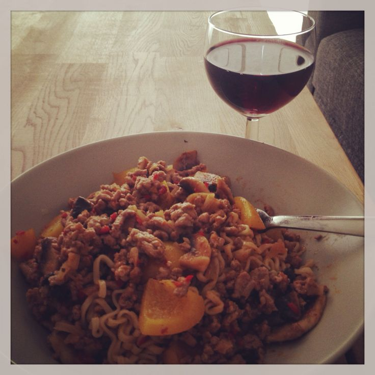 Pork nudles with veggies and a glas of red