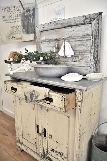 Chippy painted cabinet with zinc top and old wood backsplash.